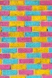 Mur de briques peint dans des couleurs jaunes, bleues et roses lumineuses Images stock