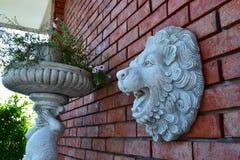 Mur de briques rouge avec Lion Face Sculpture photos libres de droits