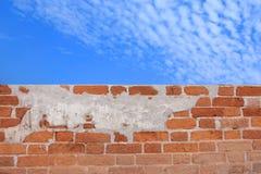 Mur de briques sous un ciel bleu nuageux photographie stock
