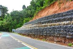 Mur de Gabion fait de pierres dans la maille en acier, utilisé comme barrière sur une pente pour l'éboulement de protection photo stock