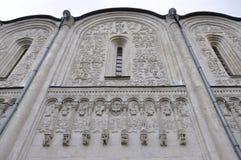 Mur de la pierre blanche avec les modèles découpés, disparaissant dans le ciel Images libres de droits