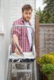 Mur de maison de peinture d'homme avec la brosse Amélioration de l'habitat de DIY Images libres de droits