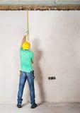 Mur de mesure de plâtre de travailleur Photos stock