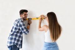 Mur de mesure de sourire de jeunes couples avec l'outil de niveau, rénovation Photos libres de droits