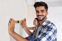 Mur de mesure de sourire de jeunes couples avec l'outil de niveau, rénovation Photographie stock