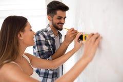 Mur de mesure de sourire de jeunes couples avec l'outil de niveau, rénovation Photo libre de droits