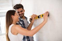 Mur de mesure de sourire de jeunes couples avec l'outil de niveau, rénovation Image libre de droits