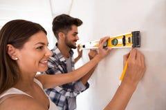 Mur de mesure de sourire de jeunes couples avec l'outil de niveau, rénovation Image stock