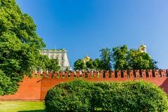 Mur de Moscou Kremlin des briques rouges, dômes d'or de la cathédrale Image stock