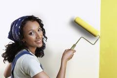 Mur de peinture de femme avec le rouleau de peinture images libres de droits