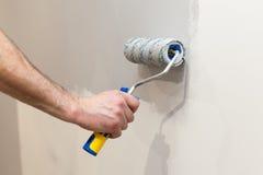 Mur de peinture de travailleur dans la chambre Murs de peinture avec un rouleau Photo stock