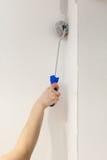 Mur de peinture de travailleur dans la chambre Murs de peinture dans un coin avec un rouleau Photos libres de droits