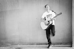 Mur de penchement d'aginst de guitariste masculin jouant la guitare acoustique Photographie stock libre de droits