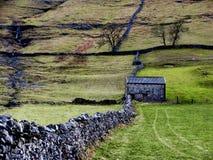 Mur de pierres sèches et grange Image stock
