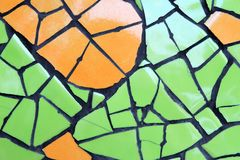 Mur des morceaux en céramique verts et de la couleur orange pour le fond Photos stock