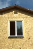 Mur des panneaux en bois avec la fenêtre en plastique blanche et le plan rapproché brun de toit Photographie stock