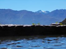 Mur empilé de roche d'étang devant la crête de montagne neigeuse Image stock