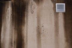 Mur en béton avec la petite fenêtre de aération couverte de mauvais temps avec des filets Image stock