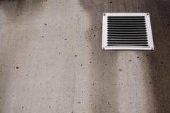Mur en béton avec la petite fenêtre de aération couverte de mauvais temps avec des filets Photos libres de droits