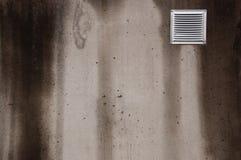 Mur en béton avec la petite fenêtre de aération couverte de mauvais temps avec des filets Photo stock