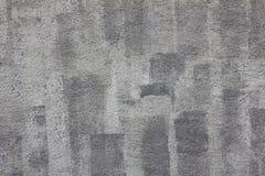 Mur en béton granulaire gris avec les filets foncés de la peinture et des taches blanches Texture de surface approximative photo libre de droits