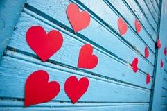 Mur en bois bleu avec les coeurs décoratifs de papier rouges Image libre de droits
