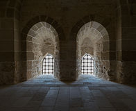 Mur en pierre avec deux fenêtres de retour allumées adjacentes avec la grille en acier Photos libres de droits