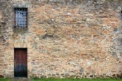 Mur en pierre avec la fenêtre barrée et la porte en bois Image libre de droits