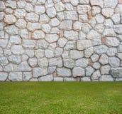 Mur en pierre avec le champ vert photos stock