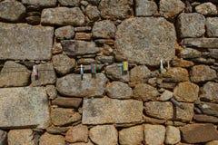 Mur en pierre avec le cintre de ficelle en métal et les pinces à linge Photographie stock libre de droits