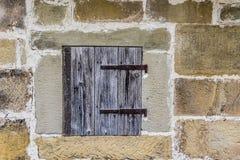 Mur en pierre avec une trappe en bois Photographie stock libre de droits