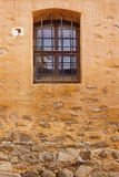 Mur en pierre de vieux jaune de bâtiment avec la fenêtre et le Rusty Bars Images stock