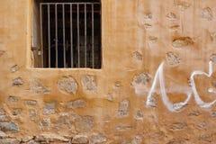 Mur en pierre de vieux jaune de bâtiment avec la fenêtre et le Rusty Bars image stock