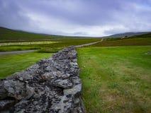 Mur en pierre divisant des champs en Islande Photos stock