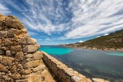 Mur en pierre du bâtiment abandonné et de la mer translucide en Corse Image stock