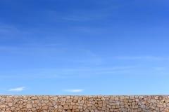 Mur en pierre et ciel bleu avec des nuages, l'espace libre de fond pour le texte Photo stock