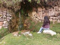 mur en pierre et femme s'asseyante photo stock