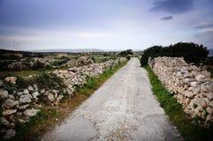 Mur en pierre rayant une route de campagne Image stock
