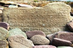 Mur et pierres de Mani avec des symboles bouddhistes Photos stock