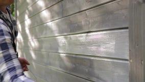 Mur extérieur de maison en bois de peinture de travailleur d'homme avec le pinceau et la couleur protectrice en bois clips vidéos