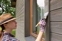 Mur extérieur de maison en bois de peinture de travailleuse avec le pinceau et la couleur protectrice en bois images libres de droits