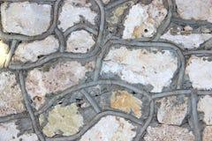 Mur fait de roches naturelles avec les frontières concrètes décoratives Photographie stock