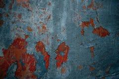Mur gris avec les fissures rouges sur le plâtre photos stock