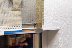 Mur isolé posé avec le plâtre, la colle, le filet, le polystyrène, la protection thermique et le filon-couche de fenêtre de plast photographie stock libre de droits