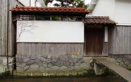 Mur japonais de maison avec la porte près du courant Photographie stock libre de droits