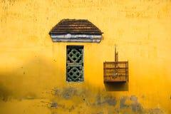 Mur jaune âgé avec la petites fenêtre et cage à oiseaux Images stock