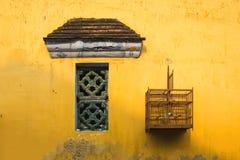 Mur jaune âgé avec la petites fenêtre et cage à oiseaux Images libres de droits