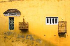 Mur jaune âgé avec la petites fenêtre et cage à oiseaux Photo libre de droits