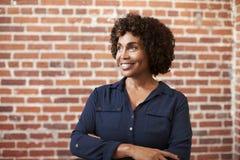 Mur mûr de sourire de Standing Against Brick de femme d'affaires dans le bureau moderne photo stock