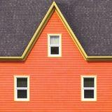 Mur orange, toit gris et châssis de fenêtre jaunes Photographie stock libre de droits
